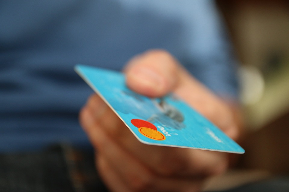 A person handing over a credit card.